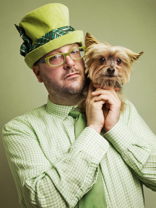 Studio portrait of man wearing green hat, green shirt, green eyeglasses holding cute Yorkie on green background