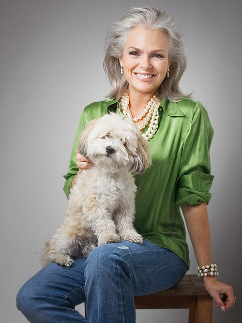 Portrait of beautiful older woman in green shirt with pearls with Havanese dog